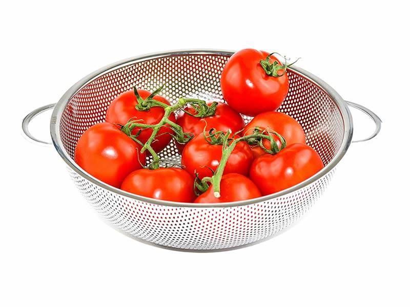 A perforated wire strainer with two handles holding fresh tomatoes.