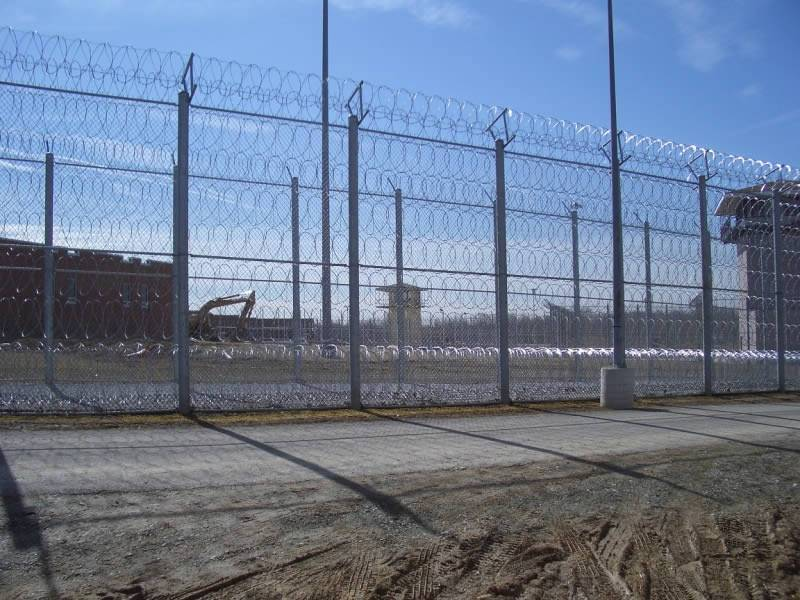 Several stories of razor wires are installed separately on the fence in a prison.