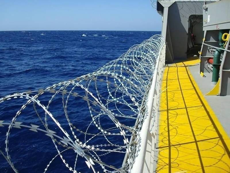 Concertina razor wire hangs on one ship rail, fixed by sturdy steel clips.
