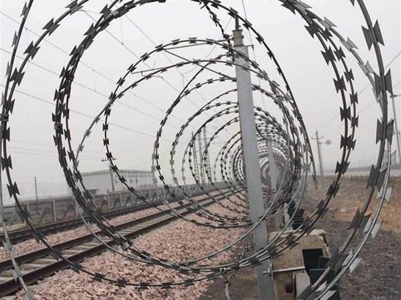 Razor wire is installed on the fence of railway track.