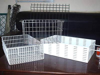 Three galvanized wire baskets on a red table, and some wire panels beside table.